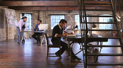 Small Business.  Casual downtown workers in chic loft or warehouse offices. Stock Footage