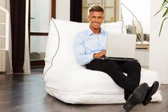 Handsome confident man sitting in armchair with laptop at home Stock Photos