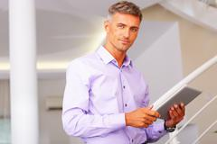 Happy mature businessman using his tablet Stock Photos