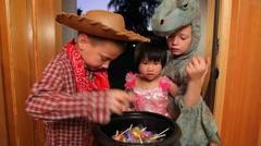 Three children grab Halloween candy Stock Footage