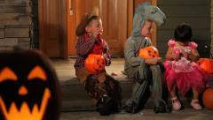 Three children in Halloween costumes sitting on porch Stock Footage