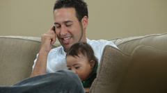Father talking on cell phone with baby - stock footage