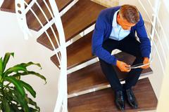 image of a man sitting on stairs with electronic tablet at home - stock photo