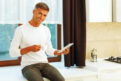 happy young man at home drinking coffee and reading news on his electronic ta - stock photo