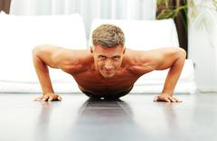 Handsome strong man doing push-ups at home Stock Photos