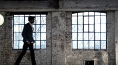A  young man in an empty loft room. Portrait of a young professional man. - stock footage