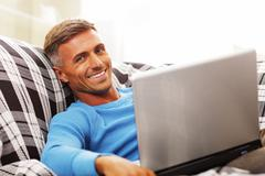 Stock Photo of handsome young man using laptop at home, sitting in armchair, smiling.