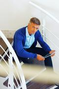 adult businessman sitting on stairs with electronic tablet browsing internet - stock photo
