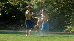 Kids playing in sprinkler, slow motion Stock Footage