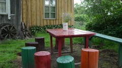 Colorfully painted stumps chairs table with vase flowers in rain Stock Footage