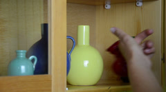 Stock Video Footage of Woman hand take small colorful crockery vases from wall cabinet
