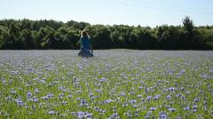 Woman walk blue cornflowers field. Recreation in farmland Stock Footage