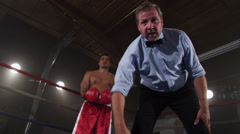 Boxing referee counting out boxer Stock Footage