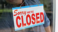 Business owner turns sign from open to closed - stock footage