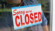 Stock Video Footage of Business owner turns sign from open to closed