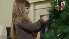 Mother and two daughters putting up Christmas tree ornaments - stock footage