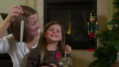 Portrait of mother and daughter holding Christmas ornaments Stock Footage