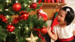 Young girl putting ornament on Christmas tree Stock Footage