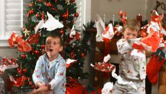Young boys throw Christmas wrapping paper, slow motion Stock Footage