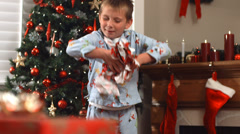 Boy throwing Christmas wrapping paper and dancing - stock footage