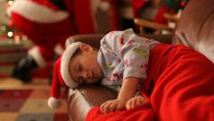 Boys sleeps on Christmas eve with Santa Claus in background - stock footage