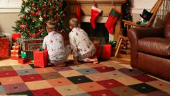 Two young boys run to gifts on Christmas morning Stock Footage
