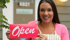 Portrait of small business owner holding OPEN sign - stock footage