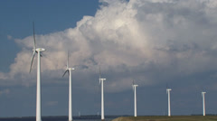 Offshore wind farm against cloudy sky + zoom out highway and dike Stock Footage