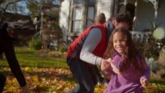 Happy mixed race family playing in autumn leaves Stock Footage