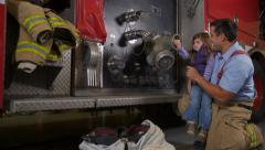 Firefighter showing young girl fire truck Stock Footage