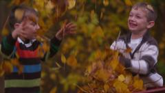 Two young boys throwing fall leaves, slow motion - stock footage