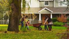 Family raking fall leaves in front of home - stock footage