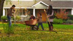 Family outdoors raking leaves in Autumn Stock Footage