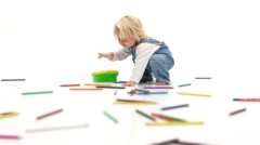 Cute young baby girl playing with colored pencils in a white studio Stock Footage