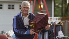 Portrait of senior man at garage sale Stock Footage
