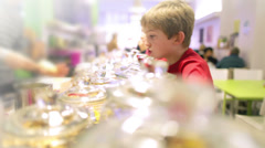 Children in a candy store exploring a variety of jars containing sweets, candy Stock Footage