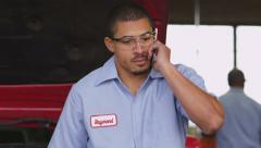 Auto mechanic talking on cell phone - stock footage