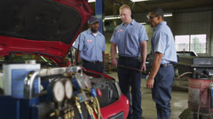 Three auto mechanics look at car together - stock footage