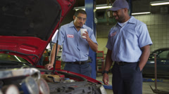 Two auto mechanics look at car together - stock footage