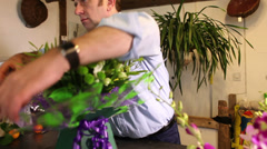 Florists small business retail shop. Florist putting together an arrangement of Stock Footage