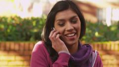 College student talking on cell phone outdoors in autumn - stock footage