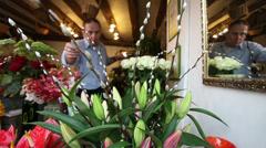 Florists small business retail shop. Florist putting together an arrangement of - stock footage