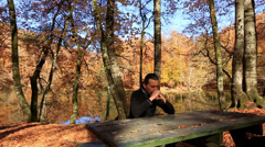 Lonely sad man at park in autumn Stock Footage