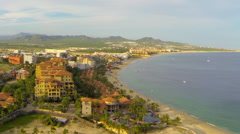 Cabo aerial Flyover of Resorts on Medano Beach at Sunset Stock Footage