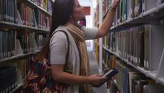 College students in library looking for books - stock footage
