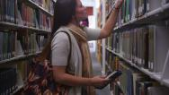 Stock Video Footage of College students in library looking for books