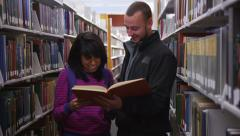 College students looking at book together in library - stock footage