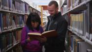 Stock Video Footage of College students looking at book together in library