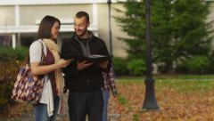 Three college students talking together on campus - stock footage