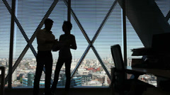 Business man and two women meet at office window with stunning view overlooking - stock footage